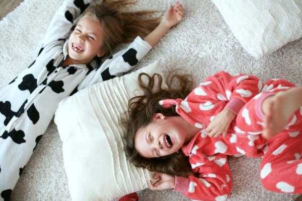 zwei lachende Kinder, liegend auf einem weißen Teppichboden
