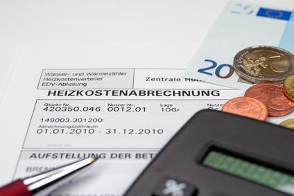 Nebenkostenabrechnung mit einem schwarzen Taschenrechner, einem silbernen Kugelschreiber und einem 20-Euro-Schein