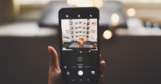 Handydisplay mit geöffneter Kamera auf eine Kerze in der Wohnung gerichtet.