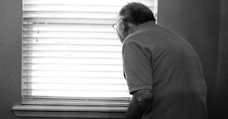 älterer Mann mit gekrümmten Rücken, der aus dem Fenster schaut