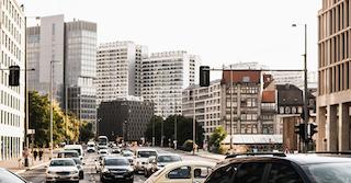 Straße in einer Stadt mit Mietpreisbremse und  vielen Autos im Vordergrund und dahinter mehrere Gebäude