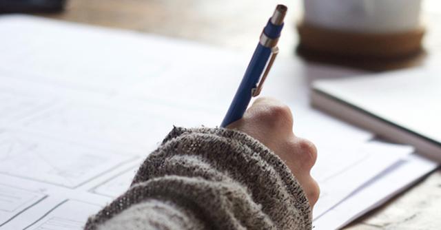 Hand eines Vermieters mit einem Kugelschreiber, schreibt Fragen an den Mieter auf ein Blatt Papier