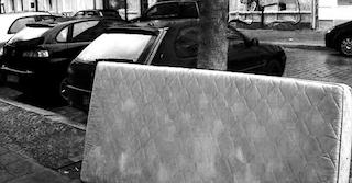 Bettmatratze lehnt als Speermüll an einem Baum auf der Straße. Dahinter befinden sich mehrere geparkte Autos. class=