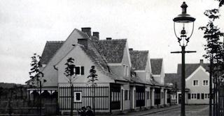 Häuserreihe aus weißen Häusern mit schwarzen Fensterläden in Berlin. Im Vordergrund steht eine schwarze Laterne