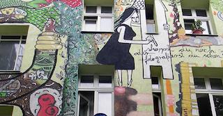 grüne Hauswand einer Wohnung, von einem Mietshäusersyndikat ,mit Zeichnungen verziert