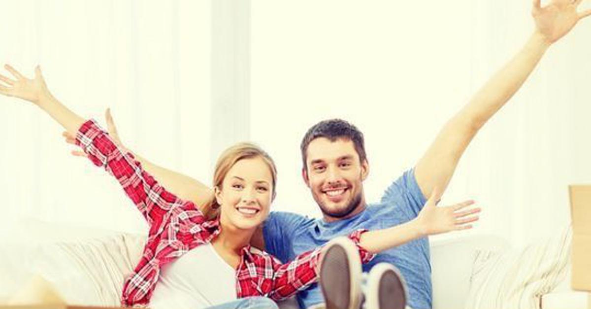 Ein Mann und eine Frau sitzen nebeneinander und strecken freudig ihre Arme nach oben.