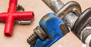 Zwei Abschnitte von Werkzeugen für Reparaturarbeiten, wovon eines blau und aus Metall ist und das andere rot und aus Plastik ist
