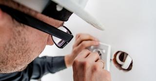 Mann mit schwarzer Brille und weißen Helm montiert eine Steckdose und hält sich Renovierungsregeln im Mietvertrag .
