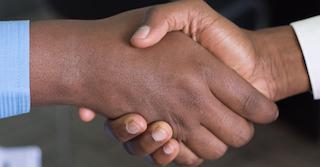 zwei Menschen geben sich gegenseitig die Hand und schließen eine Kooperation ab