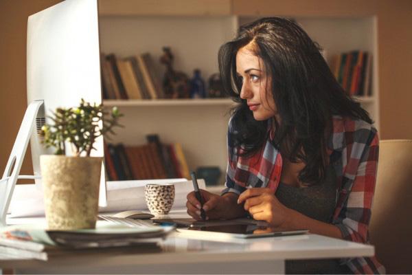 braunhaarige Frau im karierten Hemd sitzt an einem weißen Schreibtisch, vor einem Computer und schreibt etwas auf. Im Hintergrund befindet sich ein weißes Bücherregal.