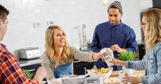 Zwei blonde Frauen und zwei braunhaarige Männer einer Wohngemeinschaft stehen in der Küche.