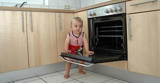 Kleinkind mit einem rot-weiß gestreiften Body, das in einer Küche aus Holz steht und sich auf der geöffneten Ofentür abstützt