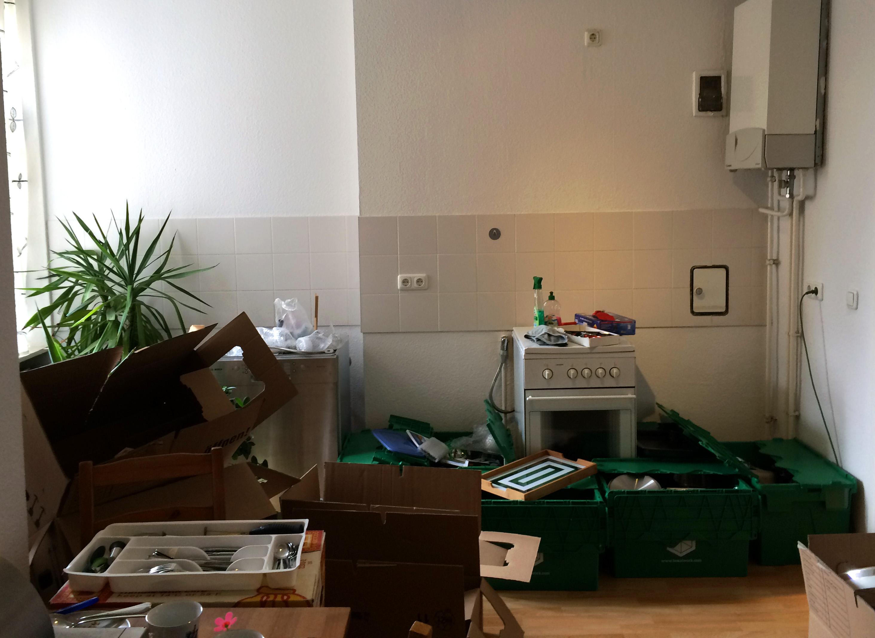 Küche in der viele grüne und aus Pappe bestehende Umzugskartons auf dem Boden stehen.