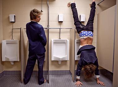 Zwei Männer im Anzug auf der Toilette. Der linke steht vor einem Pissoir und schaut dem anderen zu, welcher einen Handstand macht