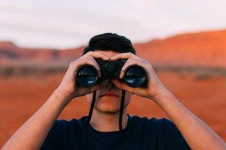 junger Mann schaut durch ein schwarzes Fernglas. Im Hintergrund sind unscharfe braun-orangefarbige Gebirge.
