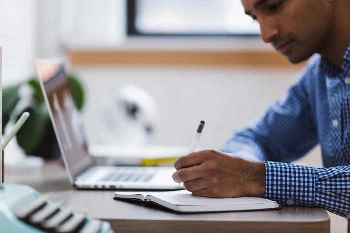 Mann im weiß-blau karierten Hemd sitzt am Schreibtisch und trägt Informationen zu einer Nebenkostenabrechnung  in den Kalender ein